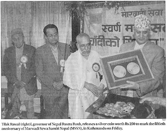 Tilak Rawal (right), govenor of Nepal Rastra Bank, releases a silver coin worth Rs 250 to mark the fiftieth anniversary of Marwa